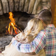 Romantic couple sitting in front of lit fireplace — Stock Photo