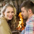 Stock Photo: Smiling young couple in front of lit fireplace