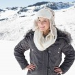 Woman in warm clothing looking away on snowed landscape — Stock Photo