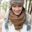 Beautiful woman wearing fur hat with woolen scarf and jacket in — Zdjęcie stockowe