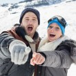 Couple in jackets pointing at the camera on snow covered landsca — Stock Photo