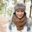 Woman wearing fur hat with woolen scarf and jacket in woods — Stok fotoğraf