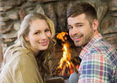 Smiling young couple in front of lit fireplace — Stock Photo