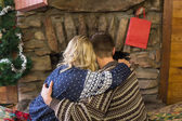 Romantic couple embracing in front of fireplace — Stock Photo