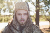 Close-up of a handsome man in warm clothing in forest — Stock Photo