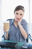 Tired casual businesswoman holding a disposable cup — Stock Photo