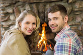 Smiling young couple in front of lit fireplace — Foto de Stock