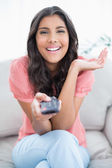 Gleeful cute brunette sitting on couch holding remote — Stock Photo