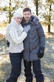 Lachende paar in winter kleding in het bos — Stockfoto