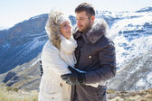 Loving couple in jackets against snowed mountain range — Foto Stock