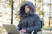Young man in fur hood jacket using laptop in forest — Foto Stock