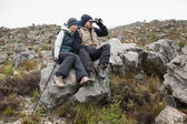 Couple sitting on rock with binoculars while on a hike — Stock Photo