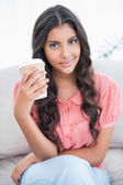 Content cute brunette sitting on couch holding disposable cup — Stock Photo