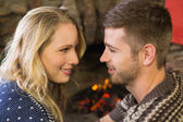 Romantic couple smiling in front of fireplace — Stock Photo