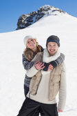 Couple in warm clothing against snowed hill — Stock Photo