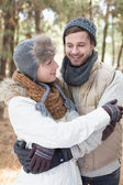 Couple in winter clothing embracing in the woods — Stock Photo