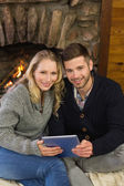 Lovely couple using tablet PC in front of lit fireplace — Stock Photo