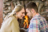 Romantic couple with eyes closed in front of fireplace — Stock Photo