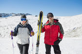 Portrait of a serious couple with ski equipment on snow — Stock Photo