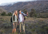 Fit young couple with backpacks on landscape — Stock Photo