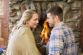 Loving couple looking at each other in front of lit fireplace — Stock Photo
