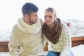 Couple in winter clothing sitting against window — Foto Stock