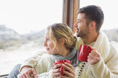 Couple in winter wear with cups looking out through window — Stock Photo