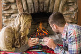 Relaxed couple with tea cups looking at lit fireplace — Stock Photo