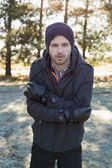 Man in warm clothing shivering while having a walk in forest — Stock Photo