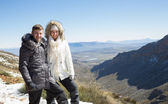 Couple in fur hood jackets against snowed mountainous valley — Stock Photo
