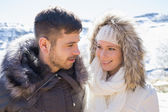 Couple in fur hood jackets against snowed mountain — Stock Photo