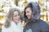 улыбаясь пара в меховой капюшон куртки в лесу — Стоковое фото