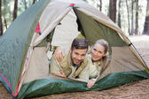 Happy couple lying in tent after a hike — Stock Photo