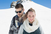Couple in warm clothing in front of snowed hill — Stock Photo