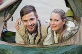 Smiling couple lying in tent after a hike — Stock Photo