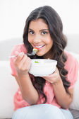 Gleeful cute brunette sitting on couch holding salad bowl — Stock Photo