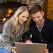Couple using laptop in front of lit fireplace — Stock Photo