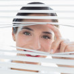 Smiling young business woman peeking through blinds — Stock Photo