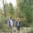 Stock Photo: Full length of fit couple exploring woods