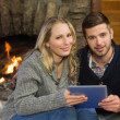 Couple using tablet PC in front of lit fireplace — Stock Photo #36271223
