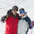 Stock Photo: Portrait of happy couple with ski boards on snow