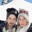 Couple in woolen hats on snow covered landscape — Stock Photo