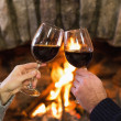 Hands toasting wineglasses in front of lit fireplace — Stock Photo