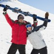 Stock Photo: Cheerful couple holding up ski board on snow