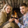 Romantic couple toasting wineglasses in front of lit fireplace — Stock Photo #36272987