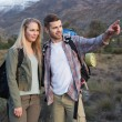 Stockfoto: Couple with backpacks standing on landscape