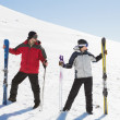 Stock Photo: Full length of couple with ski boards on snow