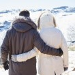 Couple in jackets looking at snowed mountain range — Foto de Stock