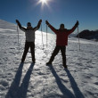Stock Photo: Silhouette couple raising hands with ski poles on snow