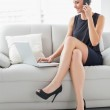 Beautiful well dressed woman using laptop and cellphone on sofa — Stock Photo #36274605